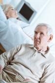 smutný starší muž a starší žena v kómatu v nemocnici