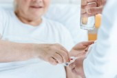 Fotografie partial view of doctor giving medicine and glass of water to patient