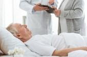 Fotografie Teilansicht des Arztes mit Zwischenablage, kranker Patient und Seniorin in der Klinik