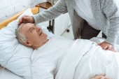 Fotografie partial view of senior woman stroking sick smiling husbend in clinic