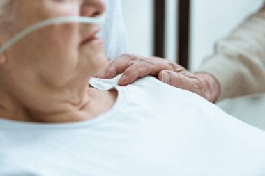 partial view of sick senior woman with husband in hospital