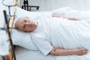 overhead view of sick senior man lying on bed in clinic