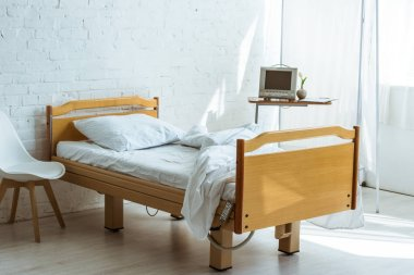 empty bed and medical equipment in hospital ward