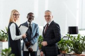 selective focus of cheerful businessmen and businesswoman standing in office
