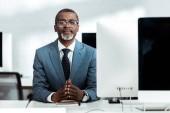 úspěšný afroamerický podnikatel s rukama sevřenými v kanceláři