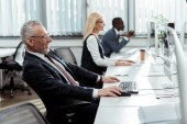 Photo selective focus of businessman in glasses smiling while working near multicultural coworkers