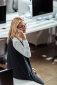 happy blonde businesswoman in glasses talking on smartphone