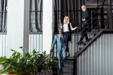 happy blonde businesswoman walking on stairs near multicultural businessmen