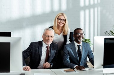 cheerful blonde woman smiling while standing near happy multicultural partners