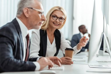 Selective focus of blonde smiling businesswoman in glasses pointing with finger while looking at coworker stock vector