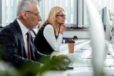 selective focus of blonde businesswoman looking at computer monitor near multicultural coworkers in office