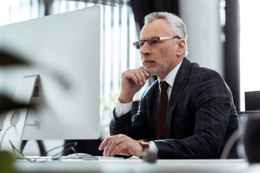 Selective focus of businessman in glasses looking at computer monitor stock vector