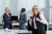 selektivní zaměření šťastné obchodní ženy oslavující triumf nedaleko multikulturních podnikatelů, kteří se třesou rukou v kanceláři