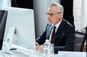 az üzletember a modern irodában dolgozó szemüvegek szelektív fókusza