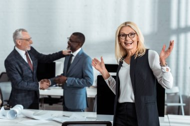 Selective focus of happy businesswoman gesturing near multicultural businessmen shaking hands in office stock vector