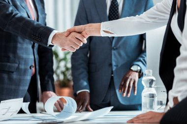 cropped view of businessman and businesswoman shaking hands near african american partner