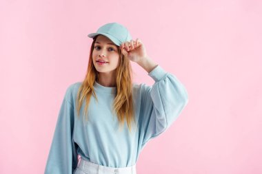 smiling pretty teenage girl touching cap isolated on pink