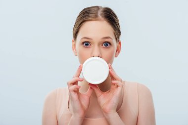 Teenage girl with obscure face holding cosmetic cream isolated on grey stock vector