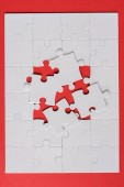 top view of white jigsaw near connected puzzle pieces on red