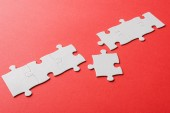 white connected jigsaw near puzzle piece on red