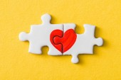 top view of connected puzzle pieces with drawn red heart isolated on yellow