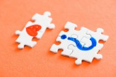 selective focus of connected puzzle pieces with drawn red heart and blue question mark on orange