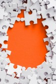 top view of frame of white puzzle pieces on orange with copy space