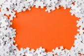 pohled shora na rám s bílými skládkami skládačky izolované na oranžovém