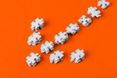 top view of direction arrow with white jigsaw puzzle pieces on orange