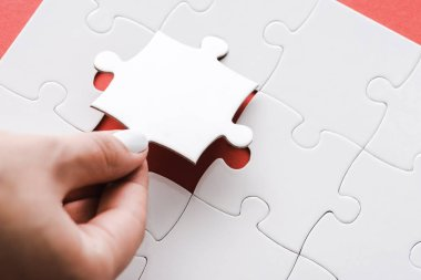 cropped view of woman holding white jigsaw puzzle piece on red