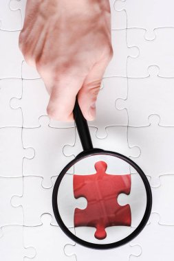 top view of man holding magnifying glass near red jigsaw near white connected puzzle pieces
