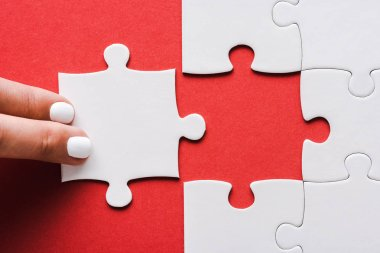 cropped of woman touching jigsaw near connected white puzzle pieces on red
