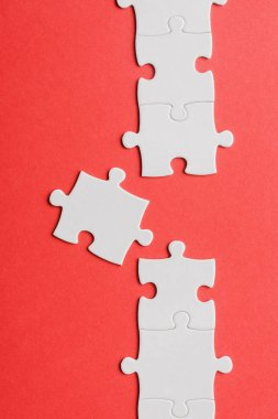 Top view of white connected jigsaw near puzzle piece isolated on red stock vector