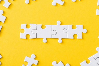 top view of connected line with white jigsaw puzzles isolated on yellow