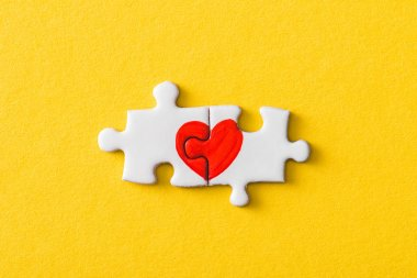 top view of connected jigsaw puzzle pieces with drawn red heart isolated on yellow