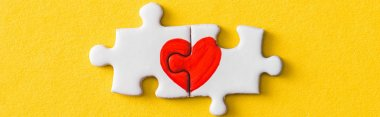 panoramic shot of connected jigsaw puzzle pieces with drawn red heart isolated on yellow