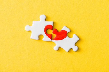 top view of jigsaw puzzle pieces with drawn red heart isolated on yellow