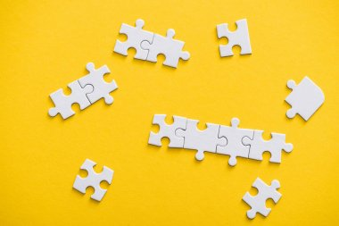 top view of connected and unfinished puzzle pieces isolated on yellow
