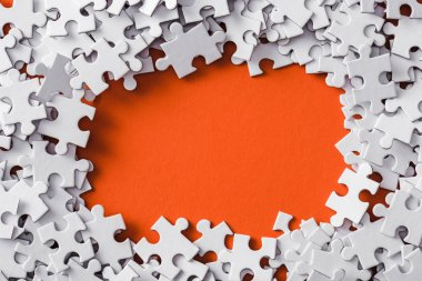 top view of frame of white jigsaw puzzle pieces on orange