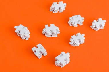 top view of stacked white puzzle pieces on orange