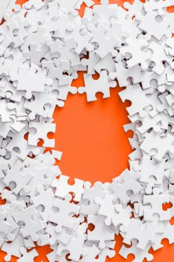 top view of pile with white jigsaw puzzle pieces on orange