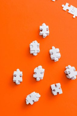 top view of stacks with white puzzle pieces on orange
