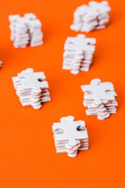 selective focus of stacks with white puzzle pieces on orange