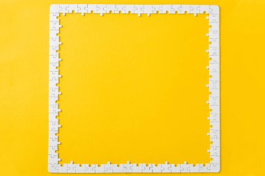 top view of frame with connected white jigsaw puzzle pieces isolated on yellow