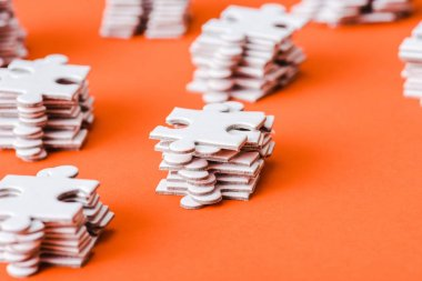 selective focus of white puzzle pieces stacks on orange