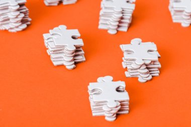 selective focus of white jigsaw puzzle pieces stacks on orange