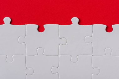 top view of matched white jigsaw puzzle pieces isolated on red