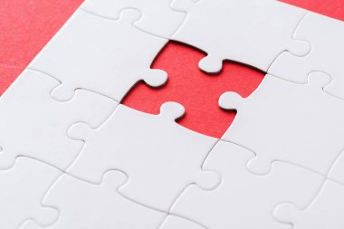 selective focus of white incomplete jigsaw on red