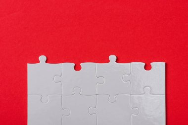 top view of connected white jigsaw puzzle pieces isolated on red