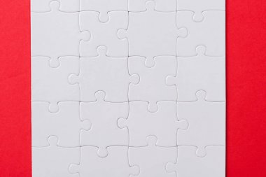 top view of set with white jigsaw puzzle pieces isolated on red